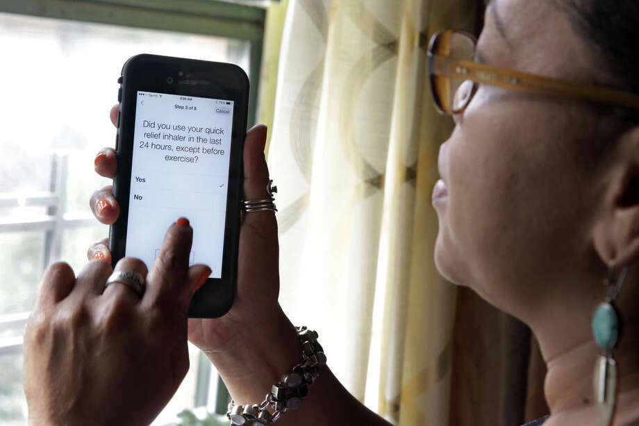 In this July 2, 2015 photo, asthma sufferer Elizabeth Ortiz, who uses the Asthma Health smartphone app daily to track her condition, poses for photos at her apartment, on New York's Lower East Side. Ortiz measures her lung power each day by breathing into an inexpensive plastic device and then typing the results into the app, which also asks if she's had difficulty breathing or sleeping, or taken medication that day. (AP Photo/Richard Drew)