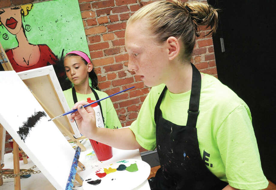 Claire McKinnon 11 and Mikaela Ortolano 10 Monday at the Art + Studio in South Norwalk for the DARE camp art lessons where local children learned painting skills. Hour photo/Matthew Vinci