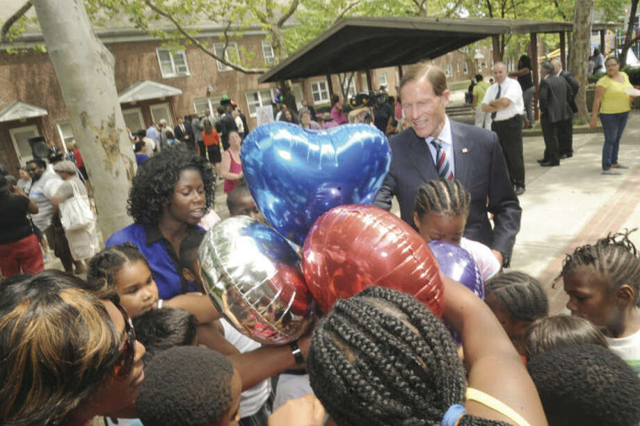 U.S, Senator Richard Blumenthal makes good on his promise to give Washington Village kids balloons from the event held there Monday where 30 million dollars was anounced to help reform the Washington Village area. Hour photo/Matthew Vinci