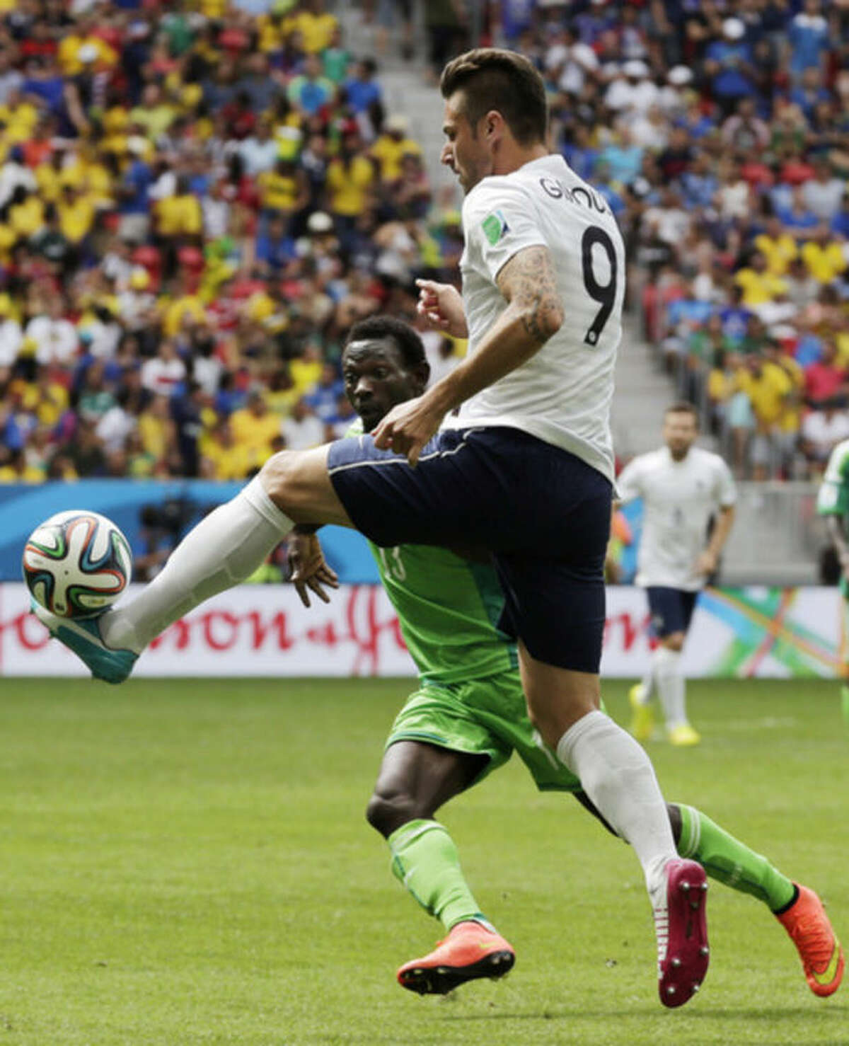 France's Olivier Giroud, right, clears the ball ahead of Nigeria's Juwon Oshaniwa during the World Cup round of 16 soccer match between France and Nigeria at the Estadio Nacional in Brasilia, Brazil, Monday, June 30, 2014. (AP Photo/Petr David Josek)