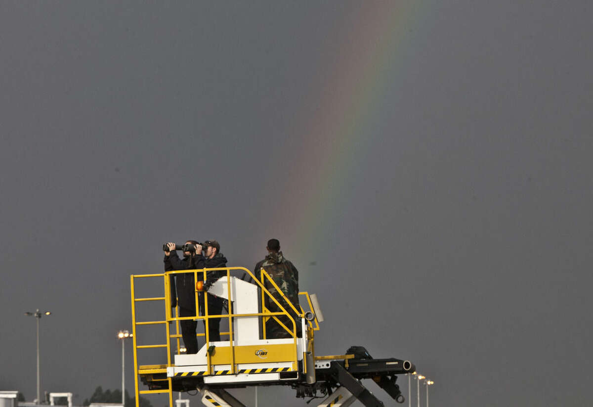 Secret Service Agents watch through their binoculars as a rainbow appears in the sky before President Barack Obama arrived at Bole International Airport, Addis Ababa, Ethiopia, Sunday, July 26, 2015. Obama is traveling on a two-nation African tour where he will become the the first sitting U.S. president to visit Kenya and Ethiopia. (AP Photo/Sayyid Azim)