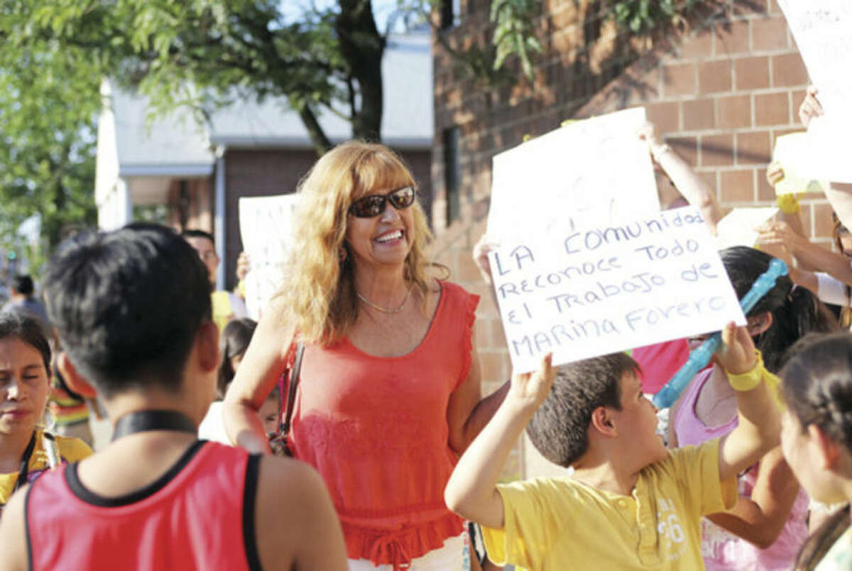 Hour photos / Danielle Calloway Marina Forero-Ferrandino is surrounded by demonstrators outside of the South Norwalk Community Center, Inc., Monday over her termination as executive director by board Chairman Warren A. Pena, shown below walking into the meeting.