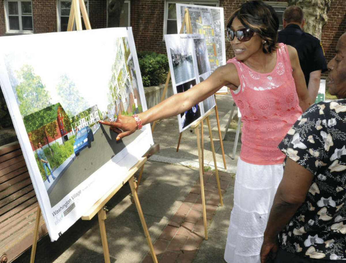 Linda Ferguson with the Washington Village Learning Center points out new construction plans that will take place in the area at a press conference Monday. Hour photo/Matthew Vinci