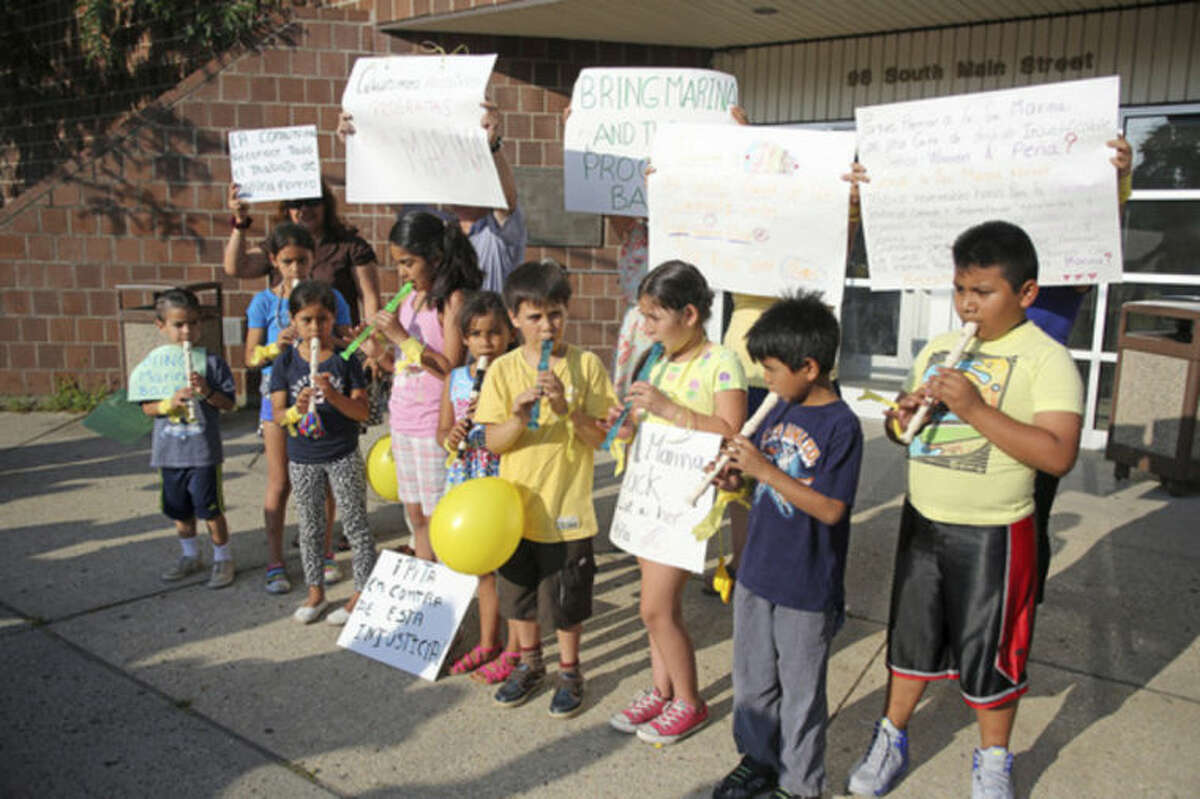 Children play music and hold signs outside of the South Norwalk Community Center, Inc., over termination of Marina Forero-Ferrandino as executive director by board Chairman Warren A. Pena. Hour Photo / Danielle Calloway