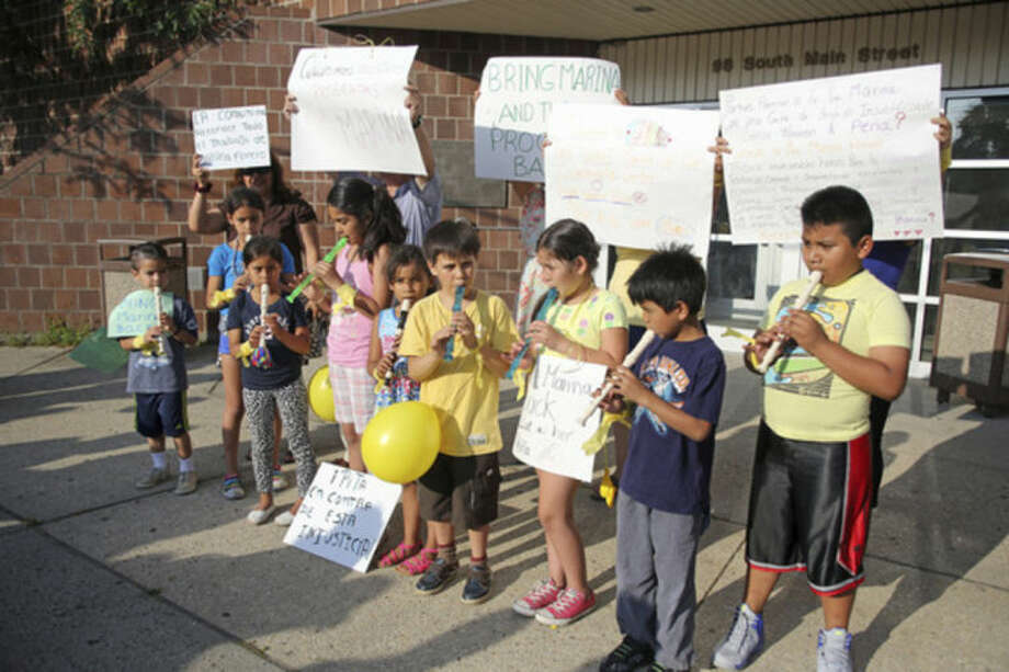Children play music and hold signs outside of the South Norwalk Community Center, Inc., over termination of Marina Forero-Ferrandino as executive director by board Chairman Warren A. Pena.Hour Photo / Danielle Calloway