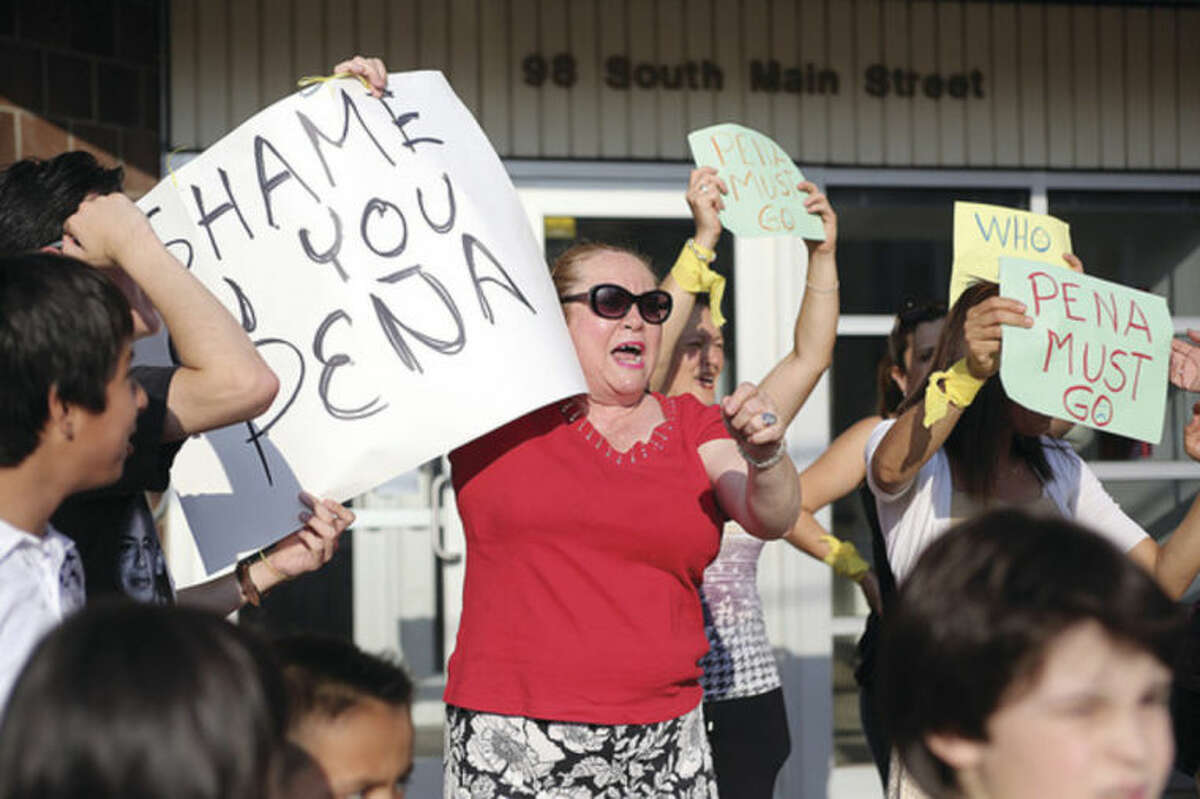 Sandy Amaya demonstrates outside of the South Norwalk Community Center, Inc., over termination of Marina Forero-Ferrandino as executive director by board Chairman Warren A. Pena. Hour Photo / Danielle Calloway