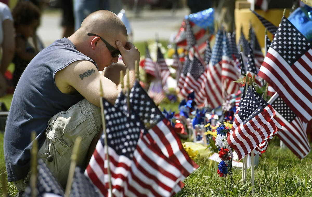 Douglas Debrs prays by a makeshift memorial outside the Armed Forces Career Center on Friday, July 17, 2015, in Chattanooga, Tenn. Counterterrorism investigators are trying to figure out why a 24-year-old Kuwait-born man, who by accounts lived a typical life in suburban America, attacked the career center and a Navy-Marine training center a few miles away in a shooting rampage that killed four Marines. (AP Photo/Mark Zaleski)