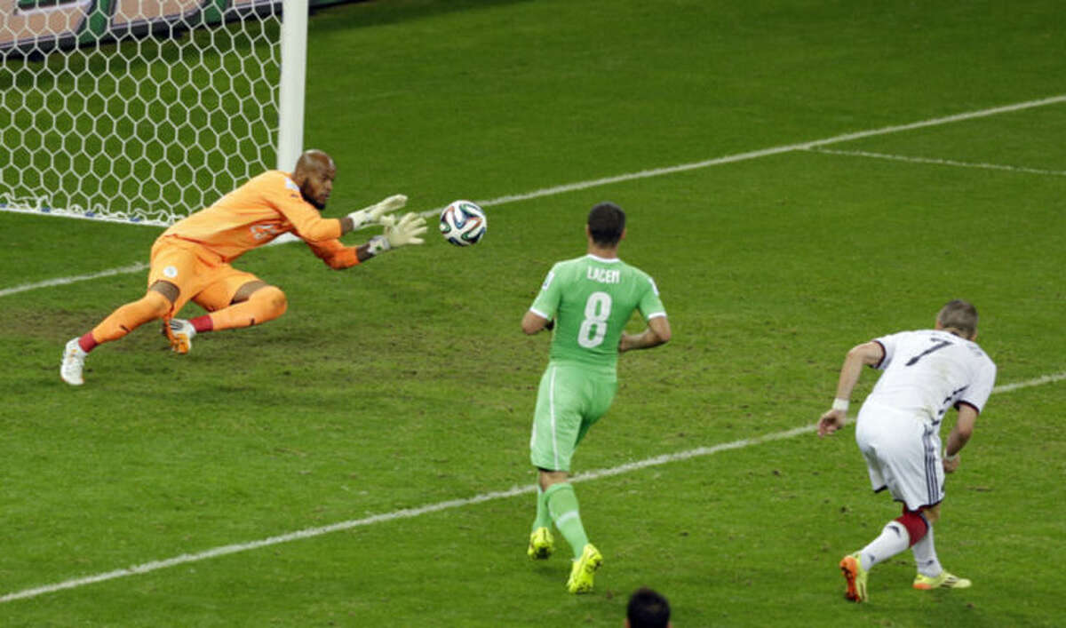 Algeria's goalkeeper Rais M'Bolhi, left, saves a header by Germany's Bastian Schweinsteiger, right, as Algeria's Medhi Lacen watches during the World Cup round of 16 soccer match between Germany and Algeria at the Estadio Beira-Rio in Porto Alegre, Brazil, Monday, June 30, 2014. (AP Photo/Thanassis Stavrakis)