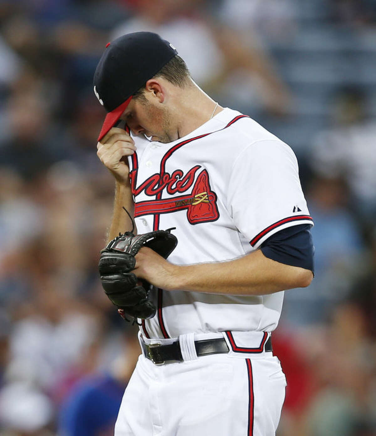 Atlanta Braves pitcher Alex Wood (40) wipes his face after loading the bases in the third inning of a baseball game against the New York Mets in Atlanta, Monday, June 30, 2014. (AP Photo/John Bazemore)