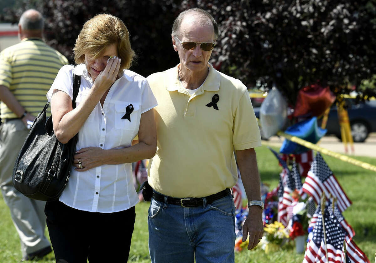 Allan Russell comforts his wife, Dee, after they visited a makeshift memorial outside the Armed Forces Career Center on Friday, July 17, 2015, in Chattanooga, Tenn. Counterterrorism investigators are trying to figure out why a 24-year-old Kuwait-born man, who by accounts lived a typical life in suburban America, attacked the career center and a Navy-Marine training center a few miles away in a shooting rampage that killed four Marines. (AP Photo/Mark Zaleski)