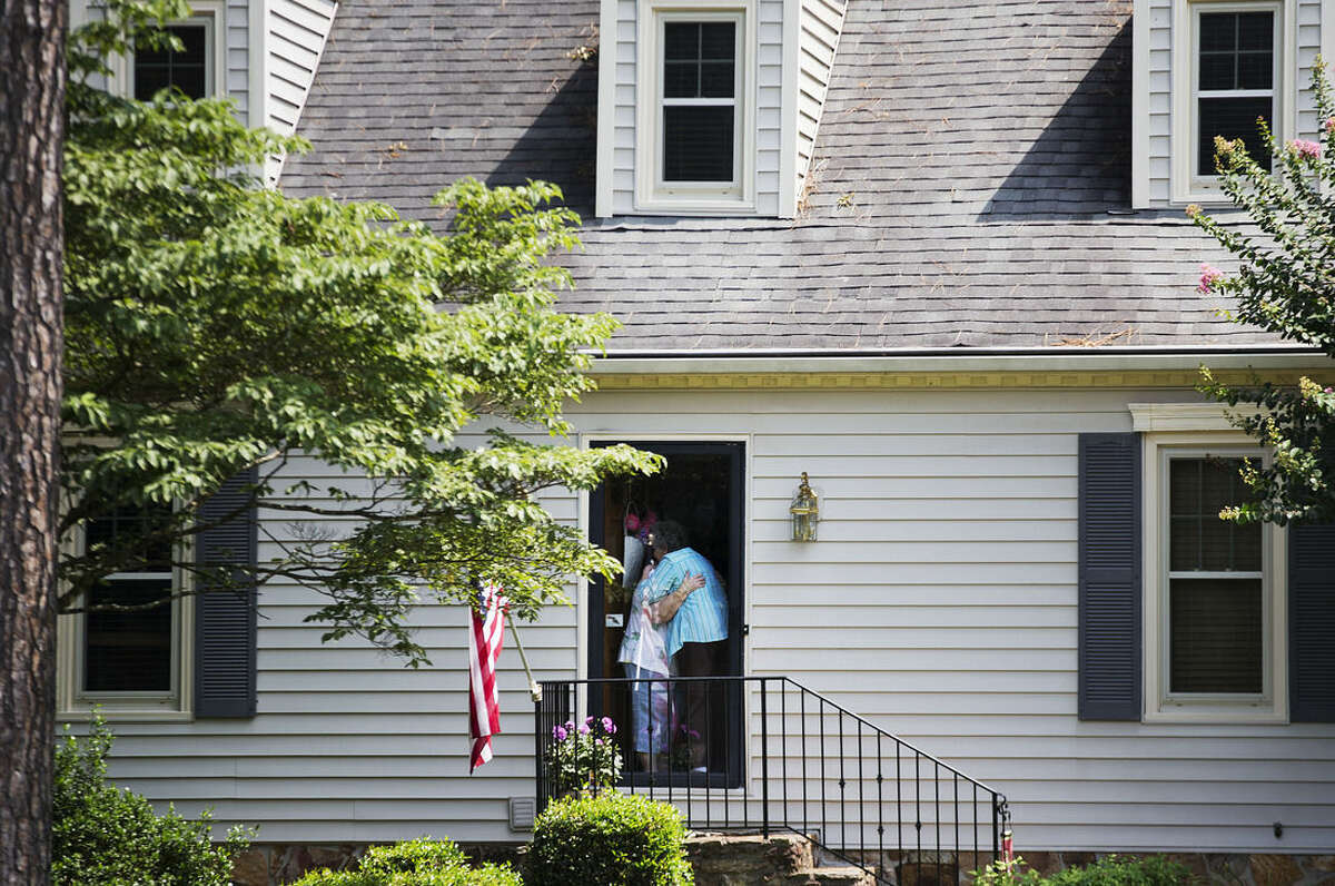 A woman at left is embraced after answering the door as mourners visit the home of Cathy Wells, the mother of Skip Wells, one of the four Marines killed in Thursday's shooting in Chattanooga, Tenn., Friday, July 17, 2015, in Marietta, Ga. (AP Photo/David Goldman)
