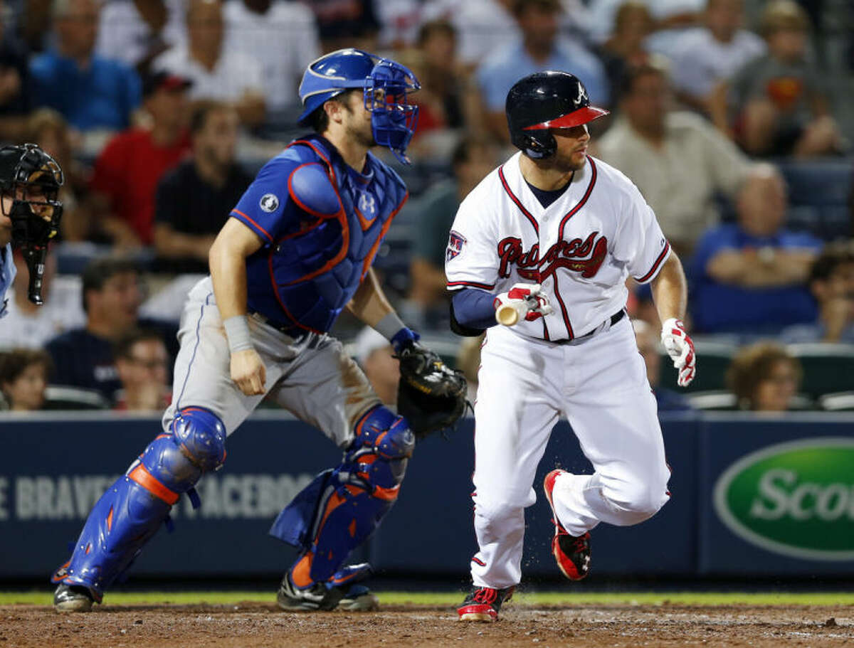 Atlanta Braves' Tommy La Stella (7) ties the game with a two-run single in the eight inning as New York Mets catcher Travis d'Arnaud (15) looks on in the eighth inning of a baseball game in Atlanta, Monday, June 30, 2014. Atlanta won 5-3. (AP Photo/John Bazemore)