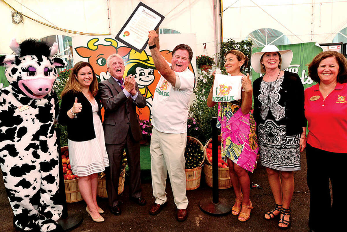 Hour photo / Erik Trautmann On behalf of the City of Norwalk, Mayor Harry Rilling, third from left, presents Stew Leonard Jr. with a Certificate of Recognition on Tuesday in celebration of the store being named the Best Grocery Store in America by BusinessInsider.com while Wow the Cow, Councilwoman Shannon O'Toole Giandurco, Lucia Rilling, Norwalk Director of Economic Development, Elizabeth Stocker and Beth Leonard Hollis look on during the brief ceremony.