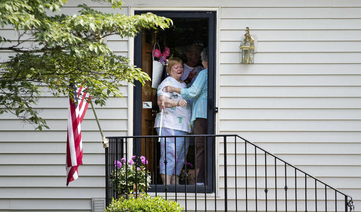 A woman answers the door as mourners visit the home of Cathy Wells, the mother of Skip Wells, one of the four Marines killed in Thursday's shooting in Chattanooga, Tenn., Friday, July 17, 2015, in Marietta, Ga. (AP Photo/David Goldman)
