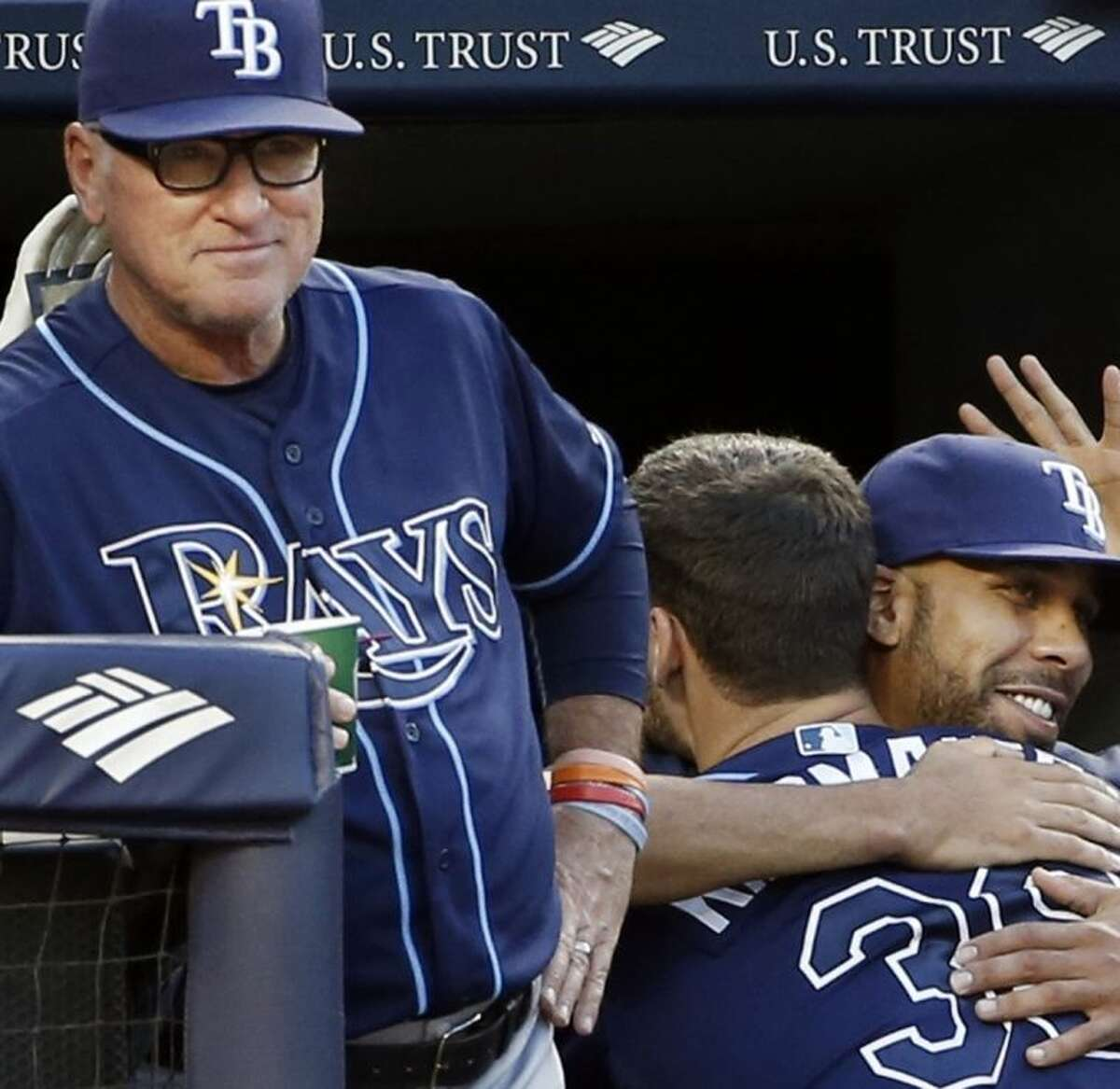Tampa Bay Rays manager Joe Maddon stands near as Rays starting pitcher David Price, right, embraces Tampa Bay Rays Kevin Kiermaier after Kiermaier hit a third-inning solo home run in a baseball game at Yankee Stadium in New York, Monday, June 30, 2014. (AP Photo/Kathy Willens)