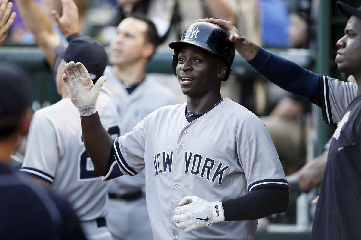 New York Yankees' Didi Gregorius is congratulated in the dugout after his two-run home run off a pitch from Texas Rangers' Matt Harrison in the third inning of a baseball game Monday,July 27, 2015, in Arlington, Texas. The shot scored Chase Headley. (AP Photo/Tony Gutierrez)