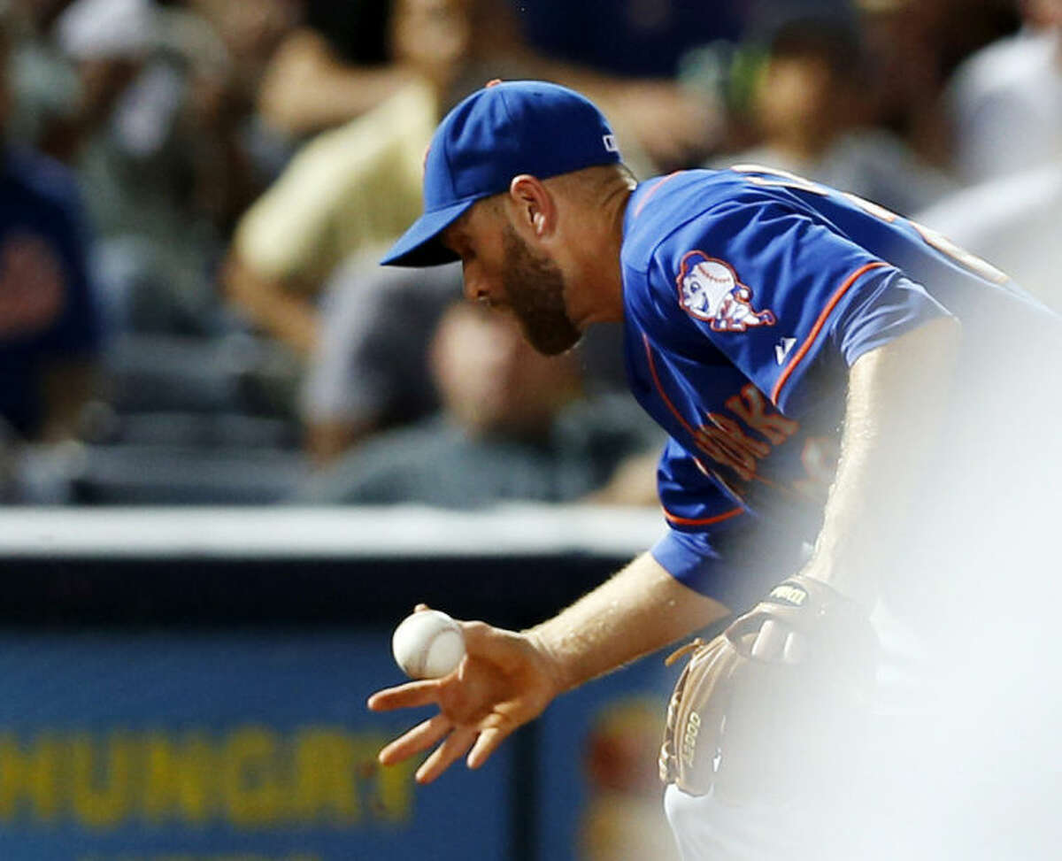 New York Mets third baseman Eric Campbell (29) has trouble fielding a ball hit by Atlanta Braves' Andrelton Simmons in the eighth inning of a baseball game in Atlanta, Monday, June 30, 2014. The go-ahead run scored on the play and Campbell was charged with an error. Atlanta won 5-3. (AP Photo/John Bazemore)