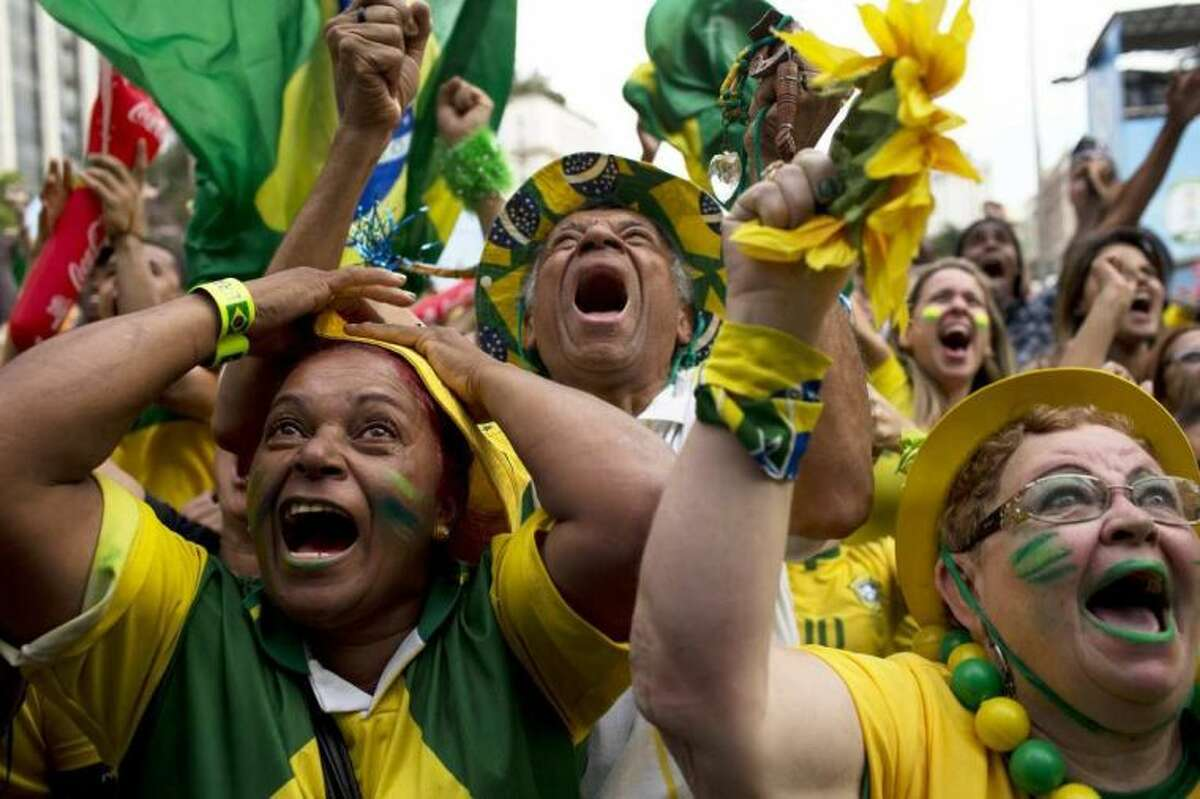 FILE - In this June 28, 2014 file photo, Brazil fans celebrate after their team scored a goal during a penalty shootout at the World Cup round of 16 soccer match between Brazil and Chile inside the FIFA Fan Fest in Sao Paulo, Brazil. Besides their deafening rendition of the national anthem, Brazilian fans haven't really used their home-ground advantage to out-sing the opposing fans. One exception is when they join together to sing ?