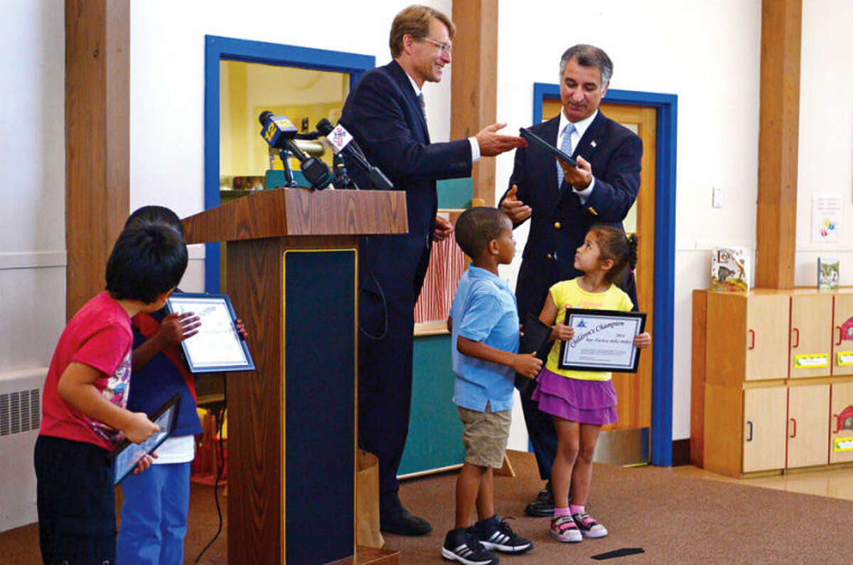 Merrill Gray, executive director of the CT Early Childhood Alliance, presents state Sen. Carlo Leone (D-27) with a Children's Champions award in recognition of early childhood legislative initiatives during a press conference Wednesday at Childcare Learning Centers in Stamford.