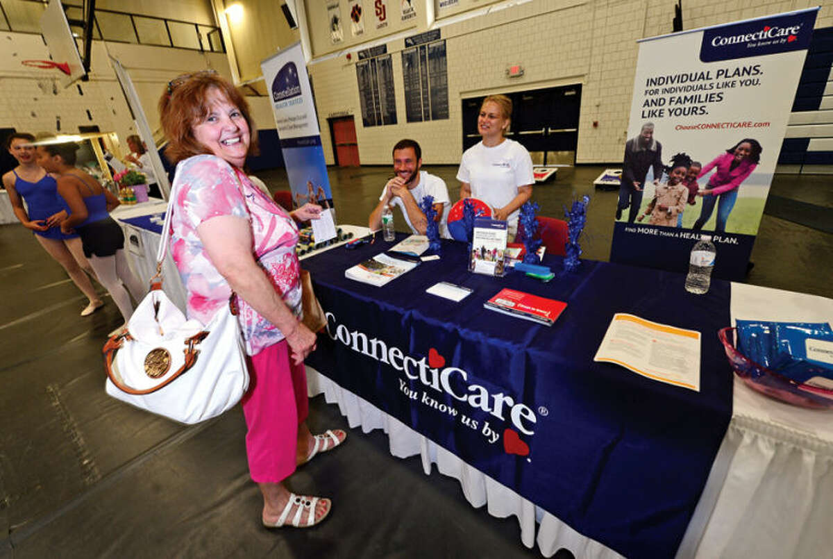 Hour photo / Erik Trautmann Emily Mazzola shares a laugh with Connecticare's Matthew Wiener and Alexandra Mensz as The Hour and Norwalk Hospital present a Family Health and Wellness Fair at Wilton High School Saturday.