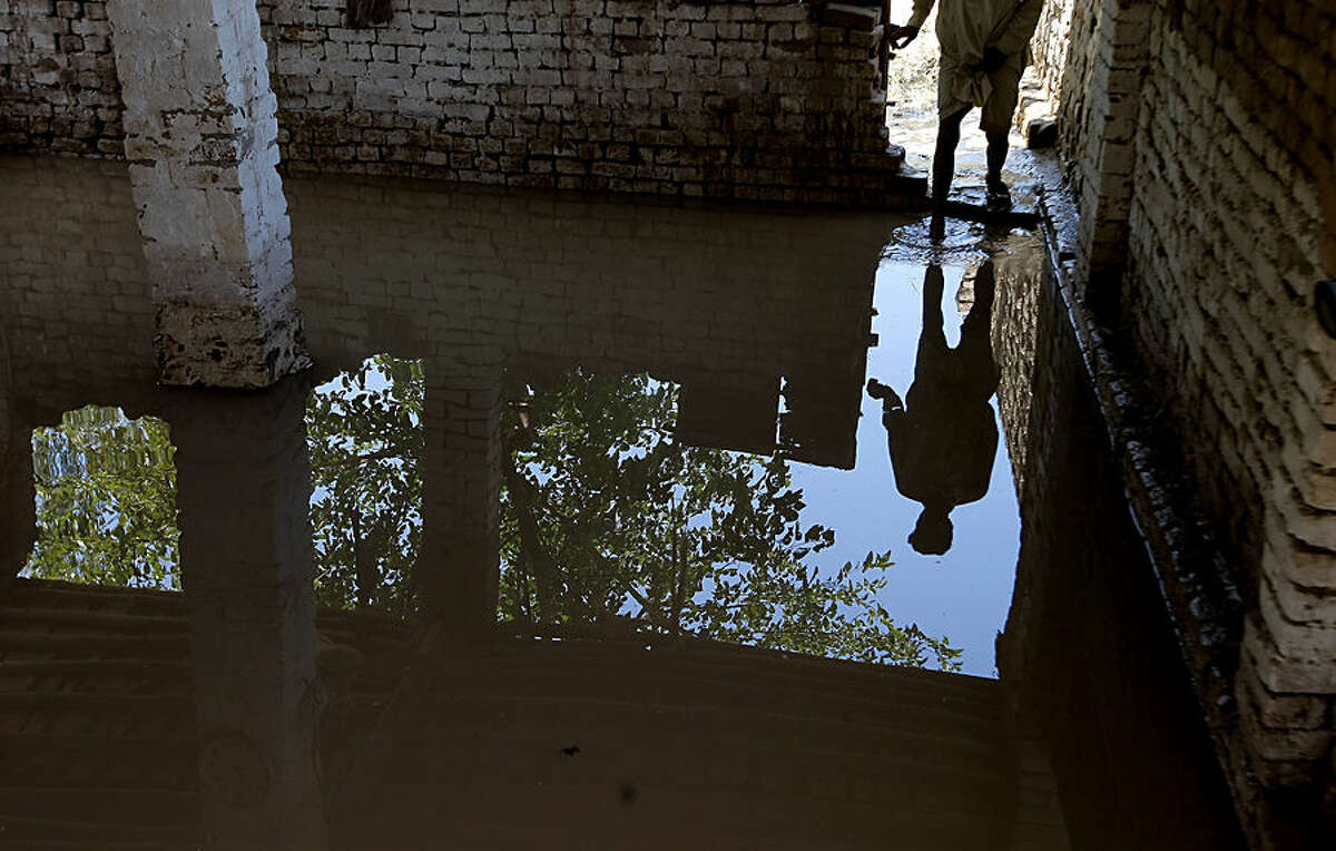 A man looks inside a mosque flooded after recent heavy rains in Peshawar, Pakistan, Monday, July 27, 2015. Heavy monsoon rains lashed an already-deluged northern Pakistan killing tens of people so far in different parts of the country. (AP Photo/Muhammad Sajjad)