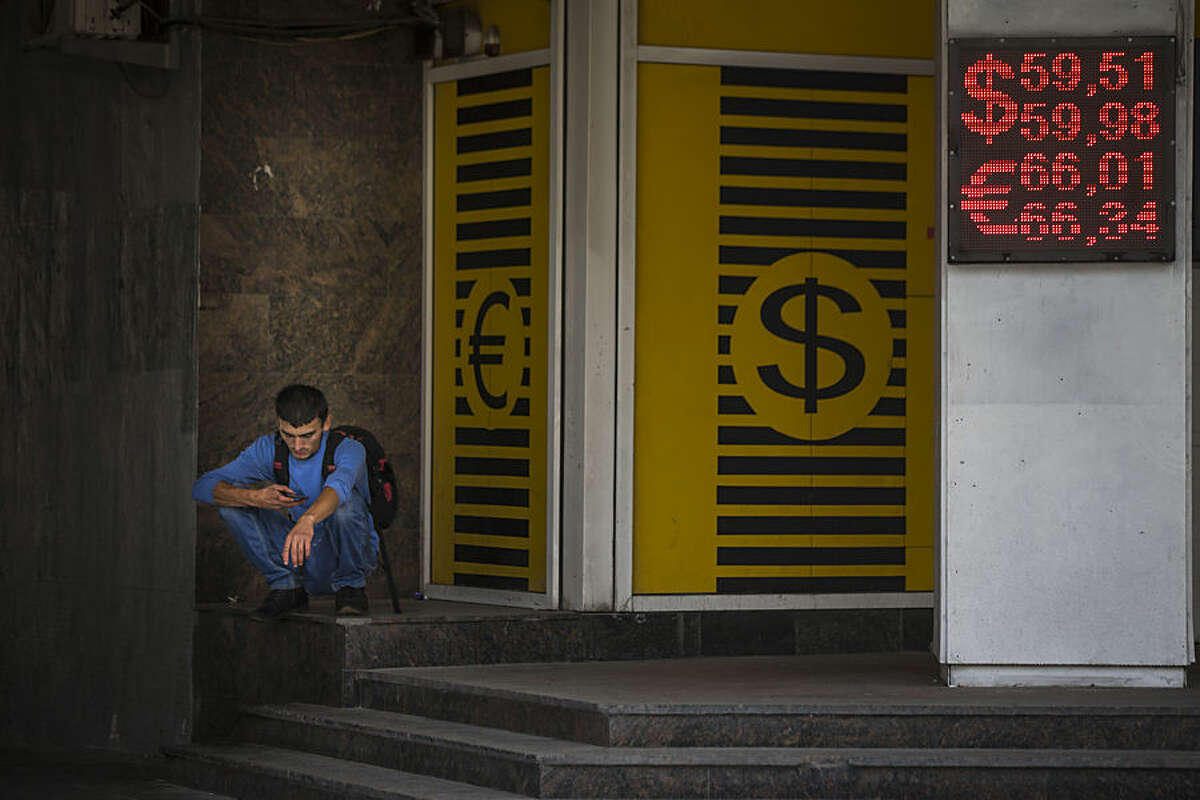 A man looks at his cell phone next to an exchange office sign showing currency exchange rate in Moscow, Russia, Monday, July 27, 2015. The Russian ruble dropped by 2 percent on Monday, to nearly 60 rubles against the dollar, battered by low oil prices.(AP Photo/Alexander Zemlianichenko)
