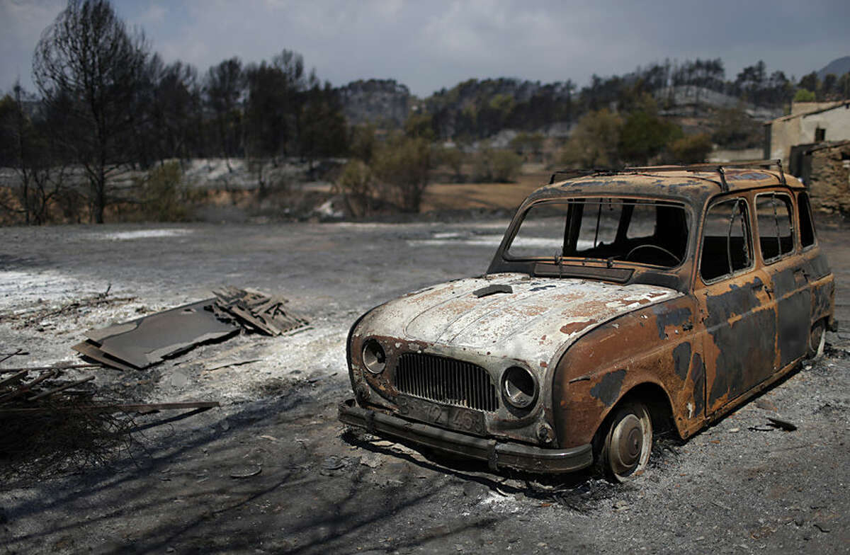 A burned car is seen after a wildfire in Sant Salvador de Guardiola, Spain, Monday, July 27, 2015. A wildfire racing through forested hills in northeastern Spain has forced the evacuation of several hundred people. The blaze broke out Sunday afternoon in dry woodland and was being fanned by steady winds. Within hours the fire had charred around 1000 hectares (2,471 acres). Firefighters said some 800 people were evacuated. (AP Photo/Manu Fernandez)
