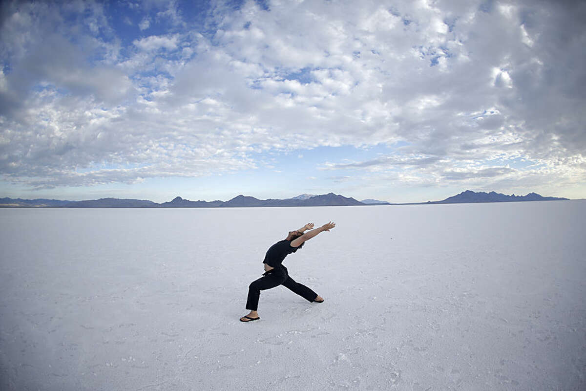 In this Wednesday, July 22, 2015 photo, Sam Evers of Houston performs his yoga on the Bonneville Salt Flats in Utah. A small city of tents, trailers and thousands of visitors appears almost every August in the Utah desert to watch cars, motorcycles and anything with wheels rocket across gleaming white sheets of salt at speeds of 400 mph. But wet weather has forced the cancellation of Speed Week for the second straight year and revived a debate about whether nearby mining is depleting the Bonneville Salt Flats of their precious resource. (AP Photo/Rick Bowmer)
