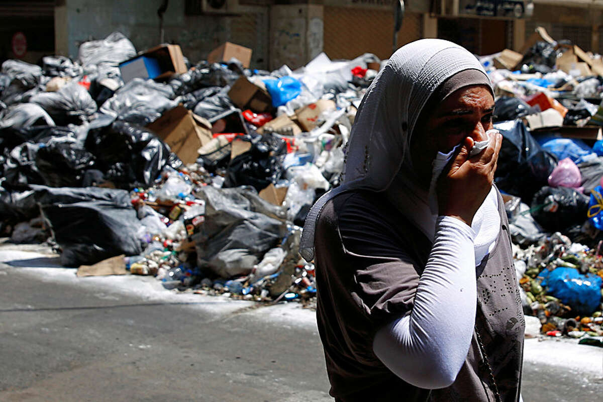 A Lebanese woman covers her nose from the smell as she walks on a street partly blocked by piles of garbage in Beirut, Lebanon, Monday, July 27, 2015. Protesters have closed the highway linking Beirut with southern Lebanon over the country's trash crisis. (AP Photo/Hassan Ammar)
