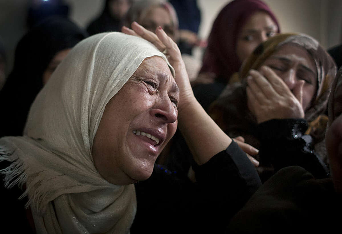 Fatima Abu Latifeh, a cousin of Palestinian Mohammed Lafi Abu Latifeh, 20, who was killed during an Israeli arrest raid, cries at the family house during his funeral procession in the Qalandia refugee camp on the outskirts of the West Bank city of Ramallah on Monday, July 27, 2015. Israeli police said the Palestinian suspected of plotting an attack in Israel was killed during the raid in the Qalandia refugee camp in the Jerusalem area. (AP Photo/Nasser Nasser)