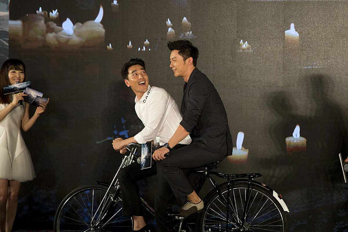 Taiwanese actor Mark Zhao, center, and Chinese actor Li Chen, right, pose for photos during a press conference for an upcoming Chinese movie
