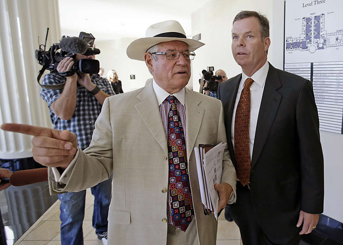 Former Utah Attorney General John Swallow, right, leaves the courtroom with his attorney Stephen McCaughey, Monday, July 27, 2015, in Salt Lake City. Swallow has pleaded not guilty to 13 charges of bribery and other crimes after prosecutors say he accepted beach vacations and use of a luxury houseboat from businessmen in trouble with regulators. (AP Photo/Rick Bowmer)
