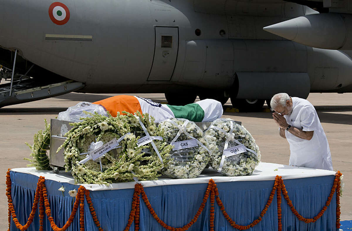 Indian Prime Minister Narendra Modi pays respect after the body of former President A.P.J. Abdul Kalam arrived at the Palam airport in New Delhi, India, Tuesday, July 28, 2015. Kalam, known as the father of the country's military missile program, died Monday after collapsing while delivering a lecture, a top state official said. He was 83. (AP Photo/Manish Swarup)