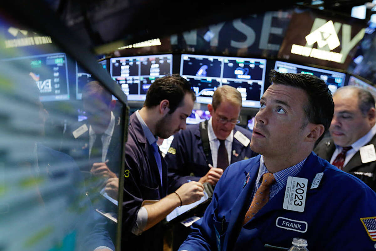 Specialist Frank Masiello, right, works with traders at his post on the floor of the New York Stock Exchange, Tuesday, July 28, 2015. U.S. stocks are opening higher after UPS, Ford and other big companies reported earnings gains and as markets in China and Europe stabilized. (AP Photo/Richard Drew)