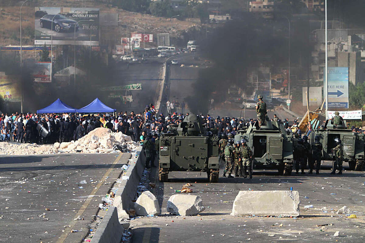 Lebanese army soldiers stand next of their armored personnel carriers as they prepare to reopen a highway linking Beirut to southern Lebanon blocked by angry protesters, in the coastal town of Jiyeh, Lebanon, Monday, July 27, 2015. The closure of the vital highway in the coastal comes amid reports that the government plans to move trash piled on the streets of Beirut to the Kharoub region south of the capital. The main company in charge of collecting trash stopped its work earlier this month amid a dispute over the country's largest trash dump. Mountains of garbage have piled up in Beirut and its suburbs. (AP Photo/Mohammed Zaatari)