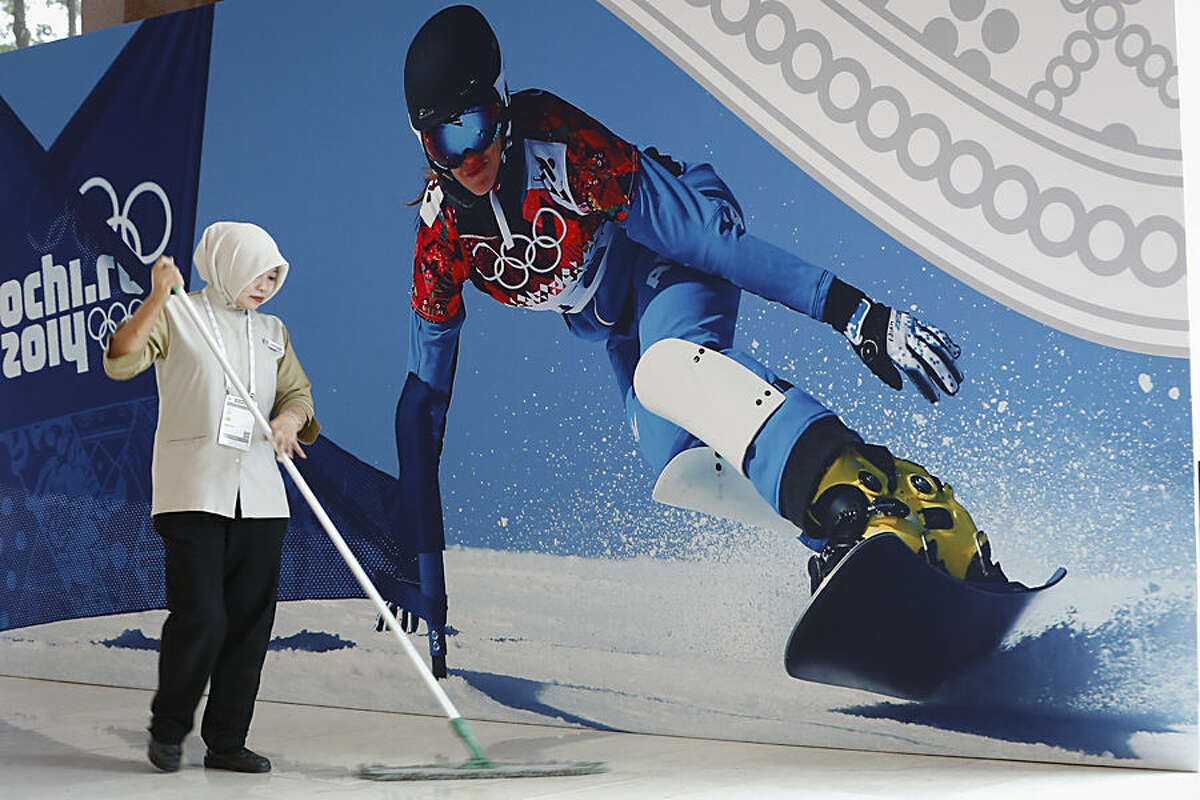 A worker cleans a floor in front of a poster at the venue that will host the 128th International Olympic Committee meeting in Kuala Lumpur, Malaysia,Tuesday, July, 28, 2015. Malaysia is hosting the 128th International Olympic Committee executive board meeting where the vote for the host cities of the 2022 Olympic Winter Games and for the 2020 Youth Olympic Winter Games will take place. (AP Photo/Vincent Thian)