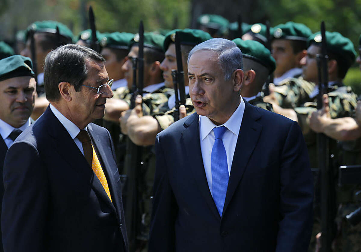 Israeli Prime Minister Benjamin Netanyahu, right, and Cyprus' president Nicos Anastasiades review a military guard of honor, during a welcoming ceremony before a meeting at the presidential palace in capital Nicosia, Cyprus, Tuesday, July 28, 2015. Israeli Prime Minister Netanyahu is on a one-day visit to Cyprus amid warming relations between the east Mediterranean neighbors and tighter energy ties following the discovery of offshore gas reserves in their respective waters. Cypriot President Nicos Anastasiades will also sound out the Israeli prime minister on his initiative to invite him and Palestinian President Mahmoud Abbas to address EU leaders at a future summit on prospects for Middle East peace. (AP Photo/Petros Karadjias)
