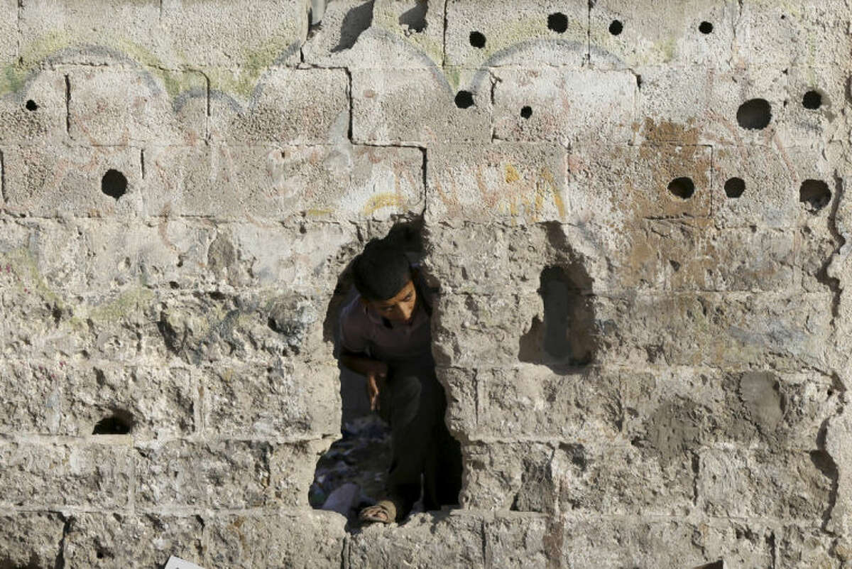 A Palestinian looks through a hole near a Hamas training camp following an Israeli air strike on it early morning in Gaza City Thursday, July 3, 2014. Israeli military carried out airstrikes on the Gaza Strip after Palestinian militants fired rockets into Israel early Thursday. The Israeli military said the air force struck 15
