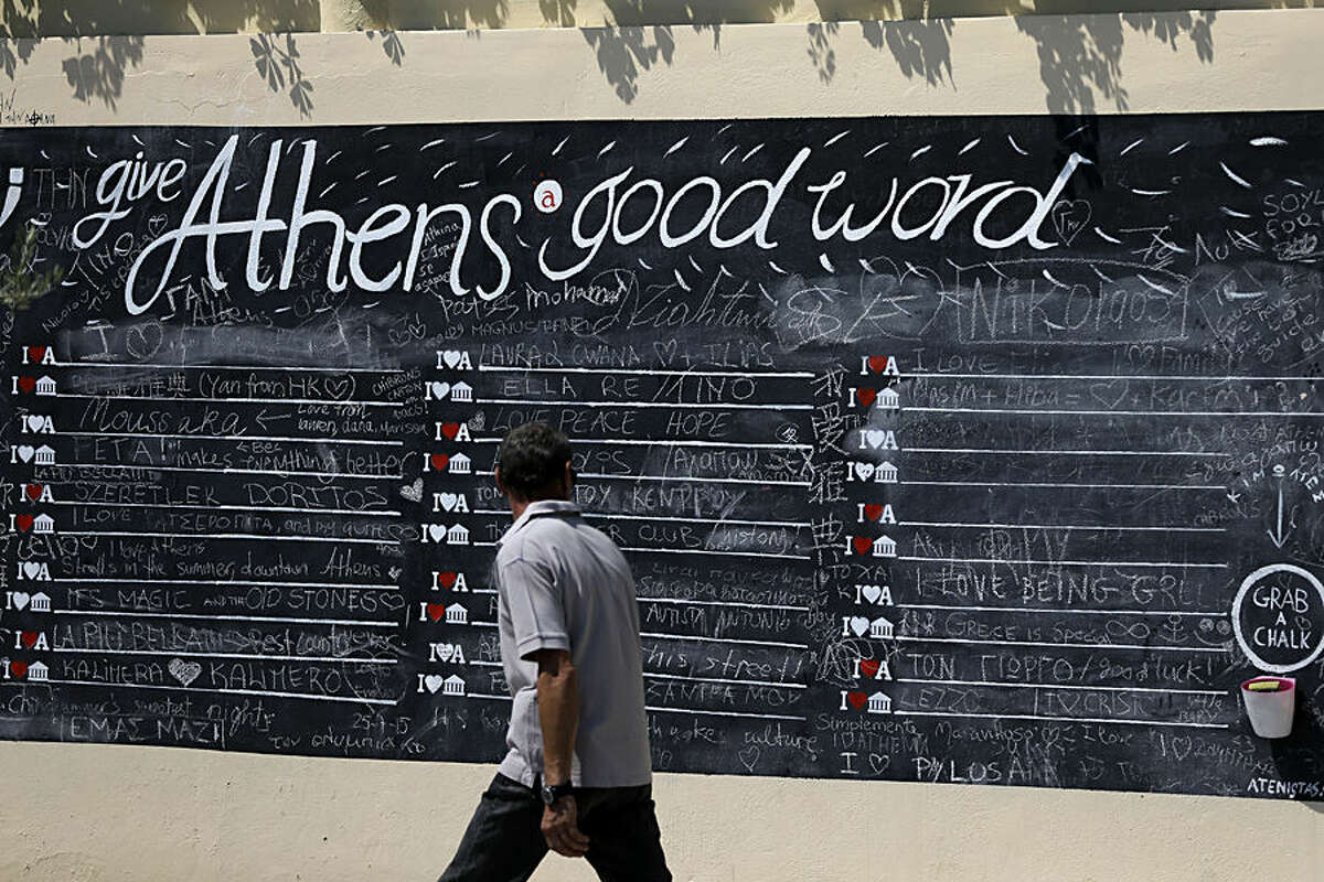 A pedestrian looks at a board where people can write their comments about the Greek capital, displayed on a wall in Athens, Monday, July 27, 2015. The government has already begun imposing new austerity measures demanded in return for the new bailout - but had relied on support from opposition parties after nearly a quarter of lawmakers in the ruling Syriza party opposed him. (AP Photo/Thanassis Stavrakis)