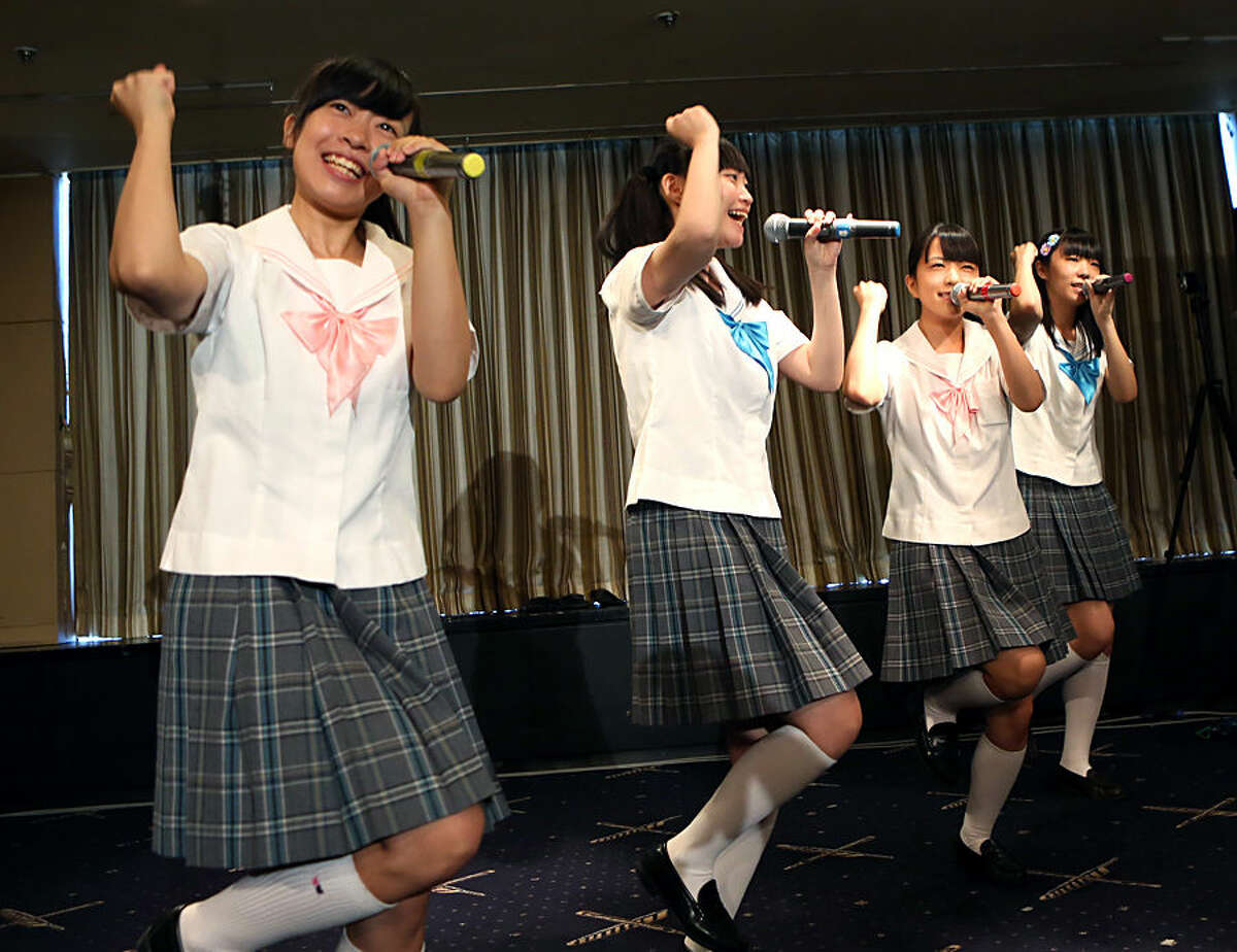 Members of pop group Seifuku Kojo Iinkai, Rina Nishino, 15, Kana Kinashi, 17, Nao Saito, 15, and Yuria Saito, 18, perform in front of foreign media in Tokyo, Tuesday, July 28, 2015. The group