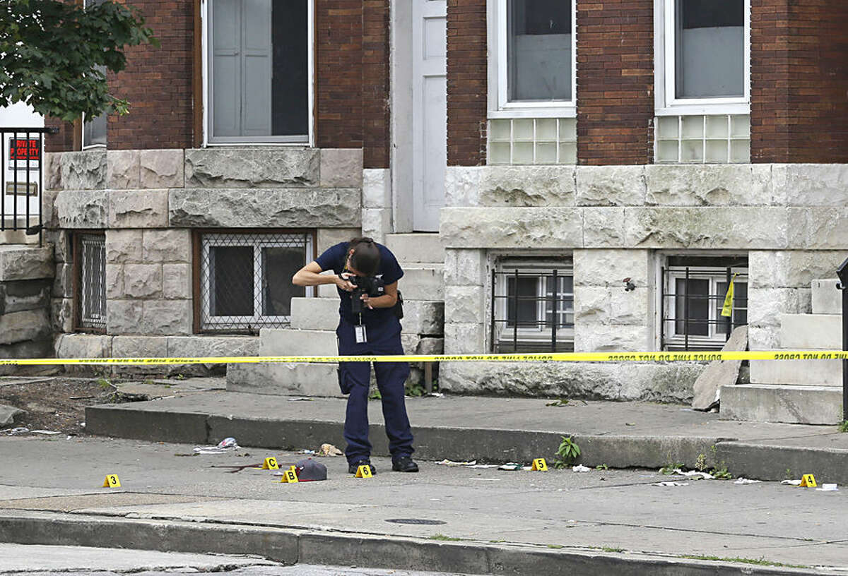 An investigator photographs the scene of a shooting, Monday, July 27, 2015, in Baltimore. Police said a male was shot in the chest near the epicenter of unrest in April following the funeral of Freddie Gray. Rioting and looting broke out in the area after the funeral of Gray, a black man who suffered a fatal spinal cord injury in police custody. (AP Photo/Patrick Semansky)