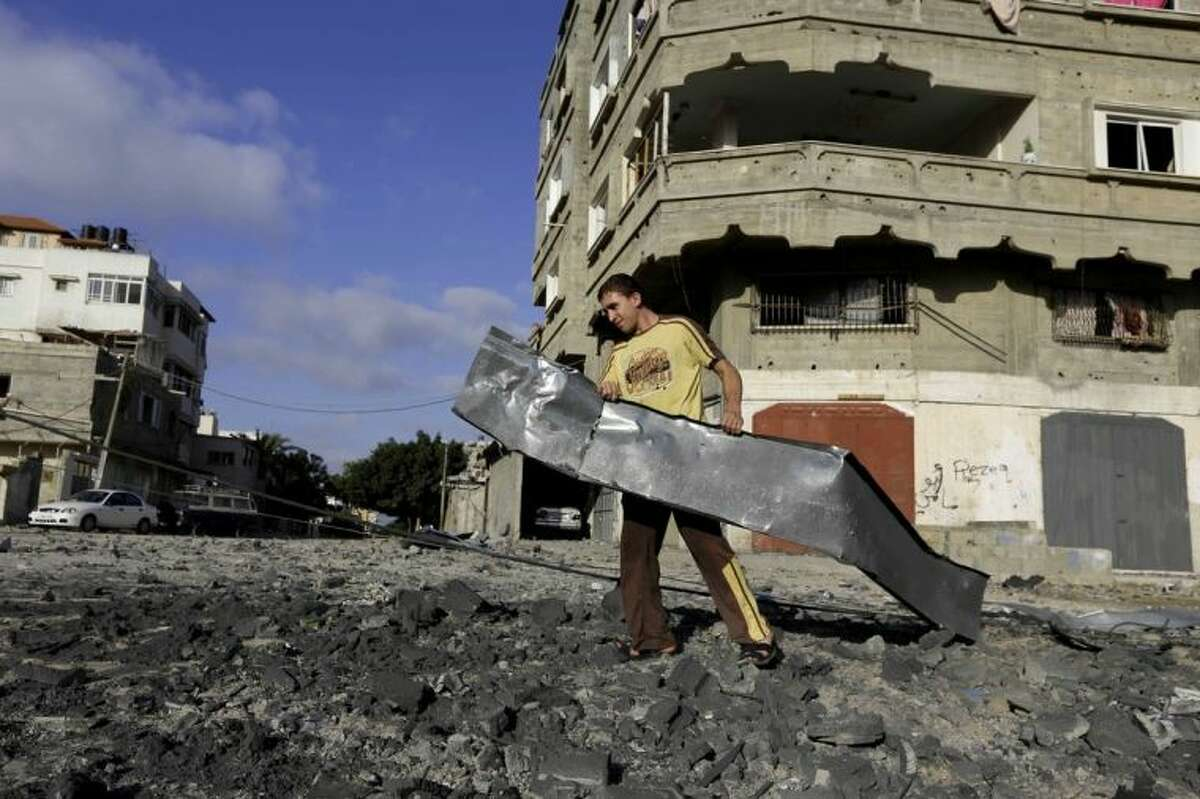 A Palestinian man carries rubble near a Hamas training camp following an Israeli air strike on it early morning in Gaza City Thursday, July 3, 2014. Israeli military carried out airstrikes on the Gaza Strip after Palestinian militants fired rockets into Israel early Thursday. The Israeli military said the air force struck 15