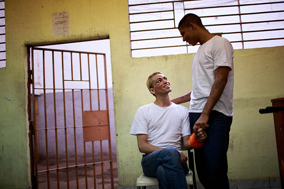 In this July 8, 2015 photo, inmate Bruno da Silva, right, holds hands with his partner, transgender inmate Danny Campos de Oliveira, inside the Evaristo de Moraes Prison, in Rio de Janeiro, Brazil. Oliveira, a 27-year-old serving an 18-month sentence for a larceny conviction, said the new rules protecting transgender inmates have already improved prison life. Before transgender prisoners were