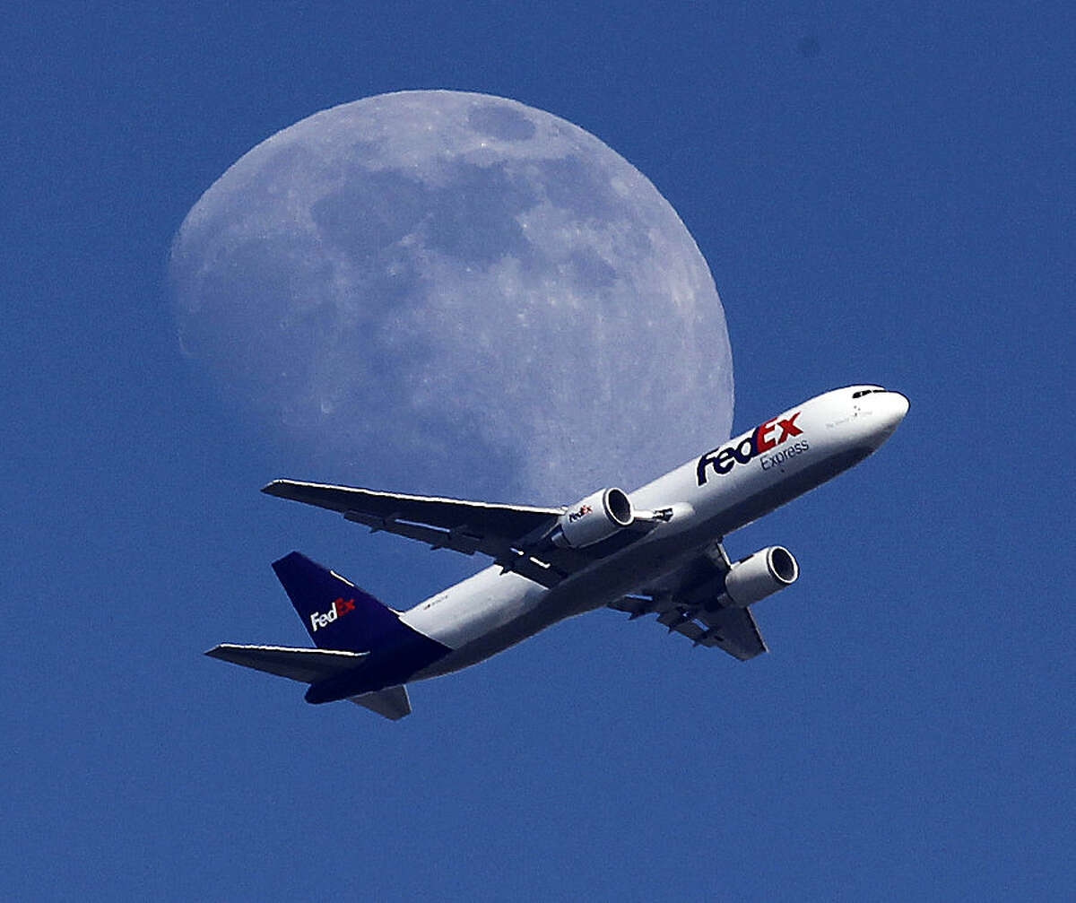 A FedEx cargo airplane passes over Whittier, Calif., on its way to Los Angeles International Airport, Sunday, July 26, 2015. (AP Photo/Nick Ut)