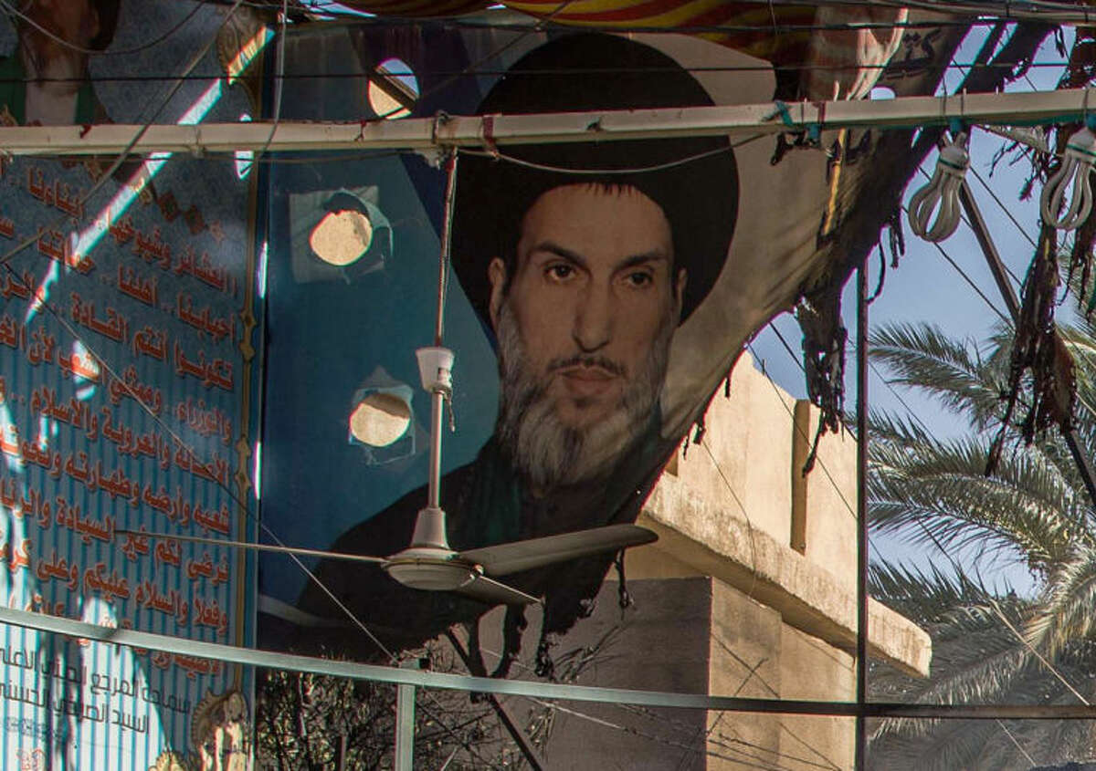 A burnt poster of Shiite cleric Mahmoud al-Sarkhi at a checkpoint in front of his home in the Shiite holy city of Karbala, 50 miles (80 kilometers) south of Baghdad, Iraq, Wednesday, July 2, 2014. (AP Photo/Ahmed al-Husseini)