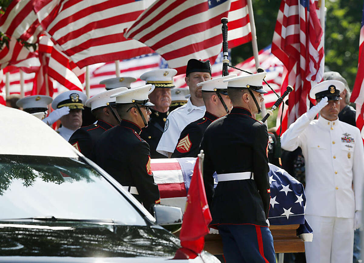 Marine pallbearers carry the casket of Marine Gunnery Sgt. Thomas Sullivan into a funeral service at Holy Cross Church in Springfield, Mass., Monday, July 27, 2015. Sullivan was one of five service members shot to death in the July 16 attack in Chattanooga. (AP Photo/Michael Dwyer)