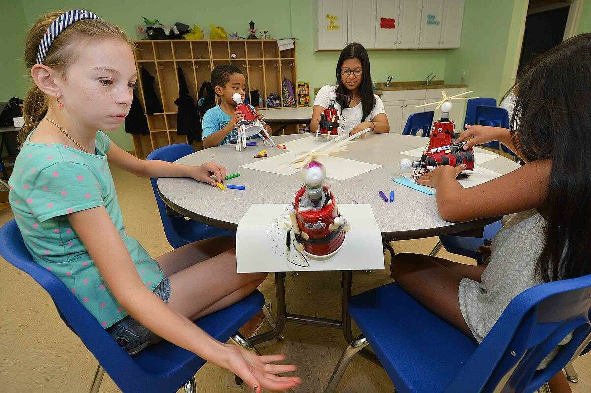 Hour Photo/Alex von Kleydorff Nina Martin catches her Art Bot as it propels itself over the edge of the table while making designs on paper during Learning for Life program at SoNo Community Cneter