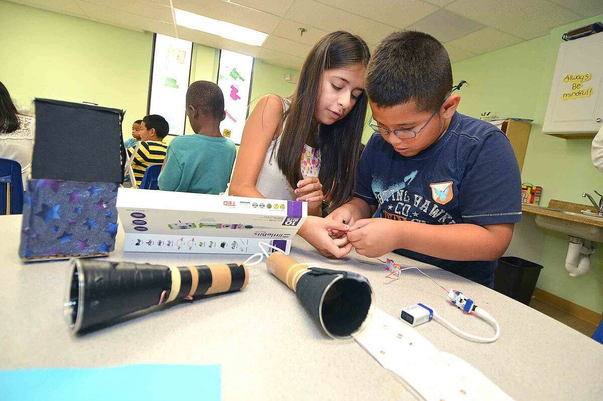 Hour Photo/Alex von Kleydorff Trisha Lopez and Marvin Lopez connect the electronics for the flashlights they are making in the Learning for Life summer enrichment program at SoNo Community Center