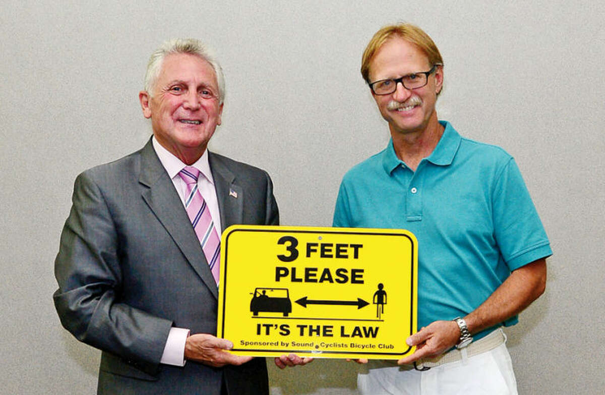 Hour photo / Erik Trautmann Norwalk mayor Harry Rilling accepts the new bicycle signs from Sound Cyclists Bicycle Club president Geoff Preu. The Club recently donated signs to the City to publicize the CT 3-foot law which mandates motorists allow at least 3 feet of separation when overtaking and passing cyclists.