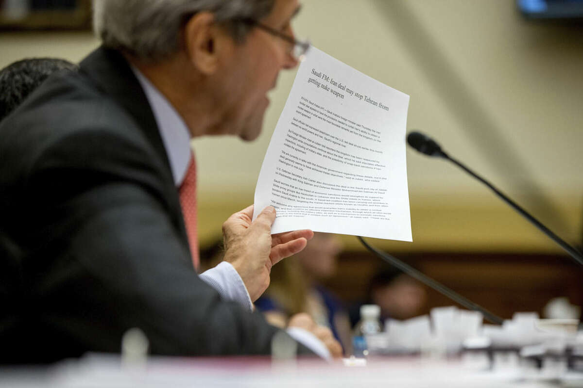 Secretary of State John Kerry holds up an article as he testifies on Capitol Hill in Washington, Tuesday, July 28, 2015, before the House Foreign Affairs Committee hearing on the Iran Nuclear Agreement. Kerry pitched the administration's controversial nuclear deal with Iran before a skeptical House Foreign Affairs Committee on Tuesday, pushing back against the allegation it would ease crippling sanctions forever in exchange for temporary concessions on weapons development. (AP Photo/Andrew Harnik)